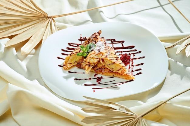 Блины с бананом, карамелью, шоколадом в белой тарелке на листе. французские крепы