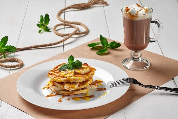 뜨거운 코코아를 곁들인 바나나 카라멜 시럽을 곁들인 팬케이크