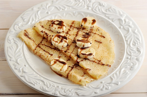 Pancakes with banana and chocolate on a plate