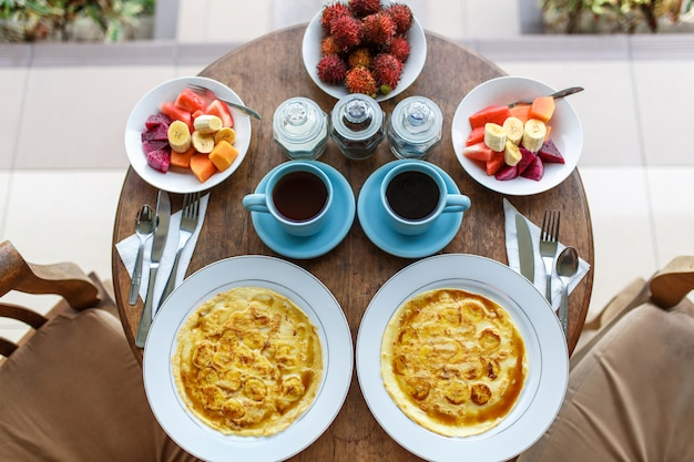 Pancakes with banana, fruits and hot coffee on wooden table.
