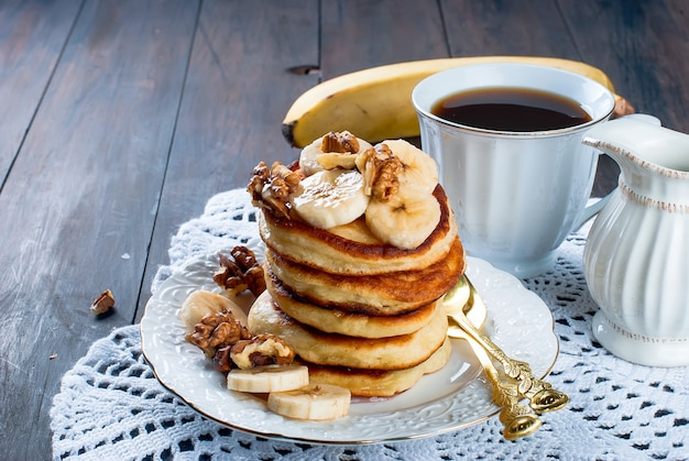 Pancakes with banana, nuts ,honey and cup coffee on dark background