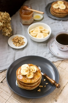 Pancakes with banana, nuts and honey, served with tea. rustic style.