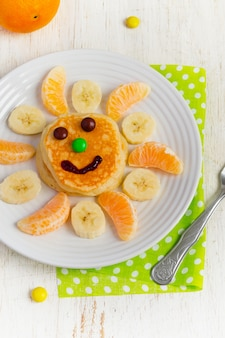 Pancakes with banana and tangerine for children. top view