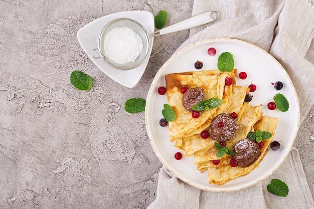 Блинчики с ягодами и шоколадом, украшенные листьями мяты