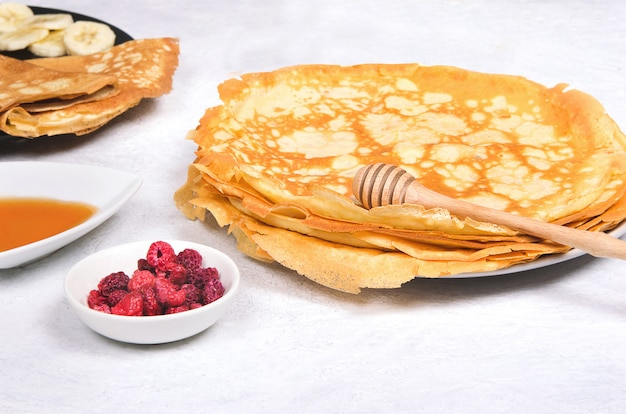Блинчики с ягодами и медом на завтрак на белом столе