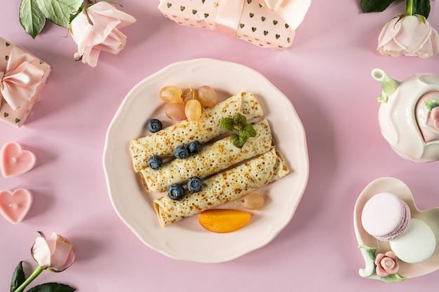 핑크 파스텔 테이블, 평면도에 딸기와 꿀 팬케이크. 분홍색 접시에 팬케이크의 축제 아름다운 봉사.