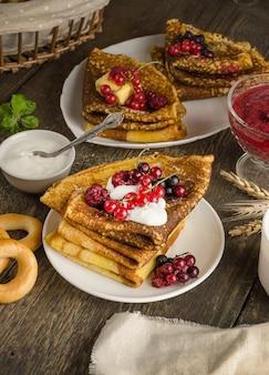 나무 표면에 러시아 maslenitsa 휴가를위한 딸기와 사워 크림이 든 팬케이크
