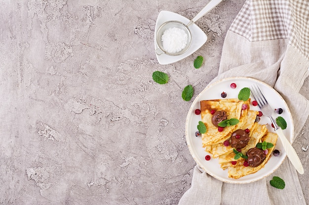 Pancakes with berries and chocolate, decorated with mint leaf