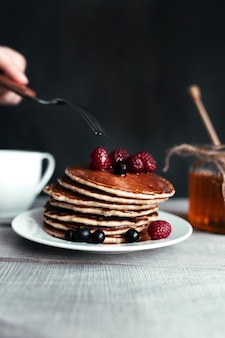 Pancakes with berries and honey on white plate, hand holding fork, spoon in jar, wooden table, cup of tea. high quality photo