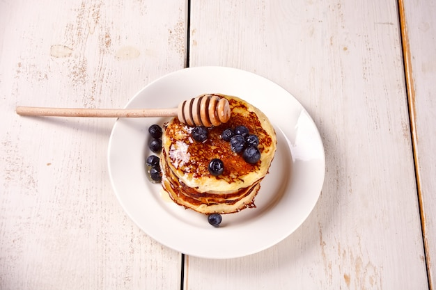 Pancakes with berries and honey on the wooden white table