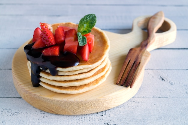 Pancakes with berries on a light background.