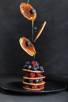 Pancakes with berries and maple syrup. flying food.
