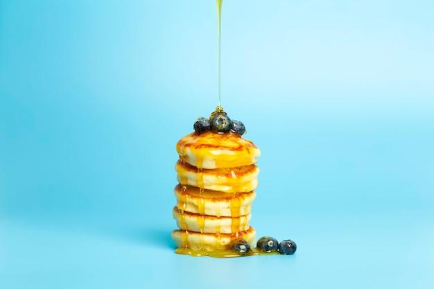 Блины с ягодами на синем фоне баннера пышные вкусные блины с черникой и сиропом ...