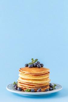 明るいパステル背景に果実とパンケーキ