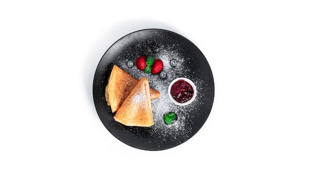 절연 베리 잼 팬케이크입니다. 검정 잉크 판에 딸기와 블루 베리 팬케이크.