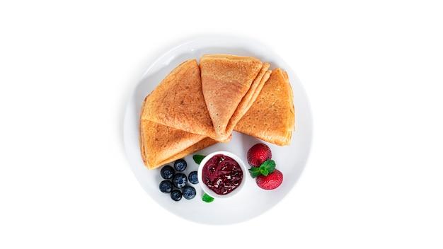 절연 베리 잼 팬케이크입니다. 딸기와 하얀 접시에 블루 베리 팬케이크.