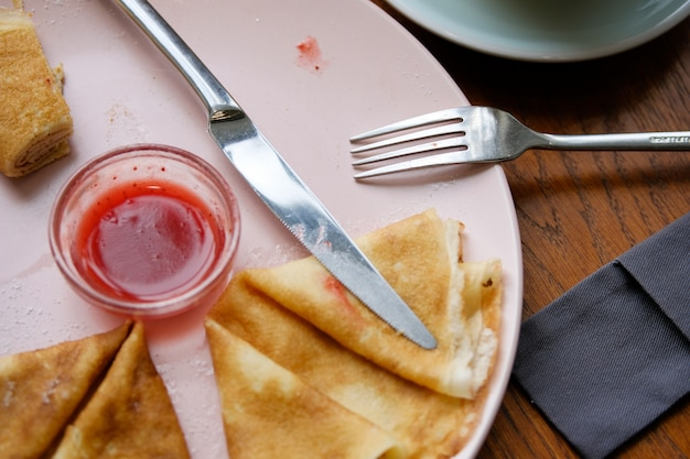 Pancakes with berry jam on a plate. near a fork and knife.