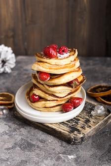 Блинчики с ягодами на белом фоне камень, рождественский десерт. блины. стопка блинов