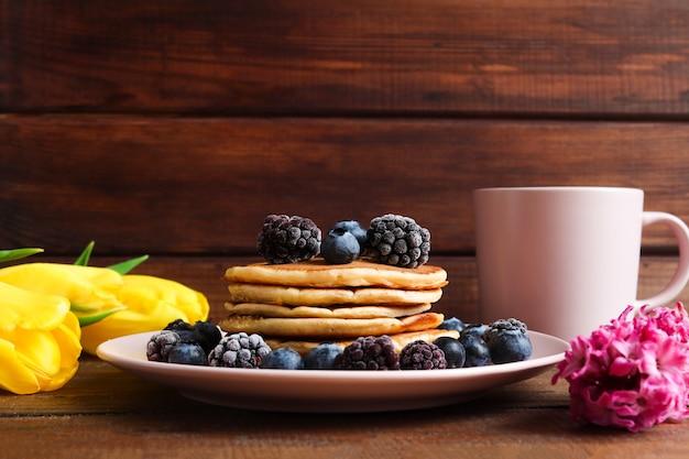 コピースペースと素朴な木製の背景にブルーベリーとブラックベリーのクローズアップとパンケーキ