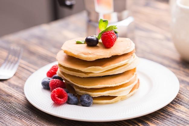 블루 베리와 나무 배경에 라즈베리 팬케이크. 아침 식사와 전통 식사.