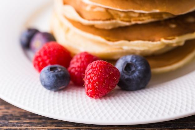 블루 베리와 나무 표면에 라즈베리 팬케이크. 아침 식사와 전통 식사.