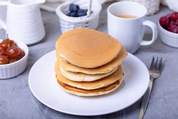 ブルーベリー、チェリー、ミニアップルジャムのパンケーキ。バックグラウンドでコーヒーとグレービーボートのカップ。伝統的なアメリカのパンケーキ。閉じる。