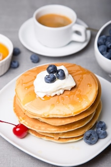 Pancakes with blueberries, cherries, sour cream, honey and coffee. close-up. selective focus.
