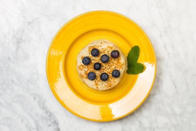 真上から見た黄色いプレートと大理石のテーブルにブルーベリーが入ったパンケーキ