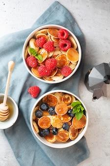 Блинчики с черникой, малиной, мятой и медом на завтрак, вид сверху
