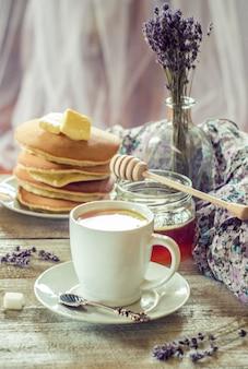 朝食にバターとハチミツとレモンティーのパンケーキ。セレクティブフォーカス