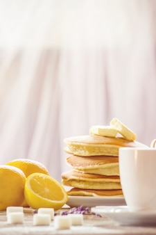 Pancakes with butter and honey and lemon tea for breakfast. selective focus.