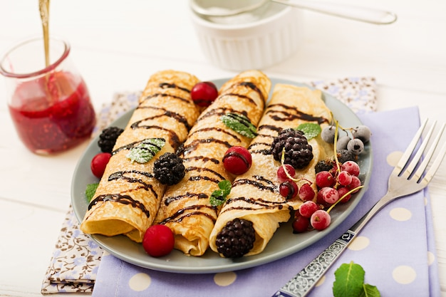 Pancakes with chocolate, jam and berries. tasty breakfast.