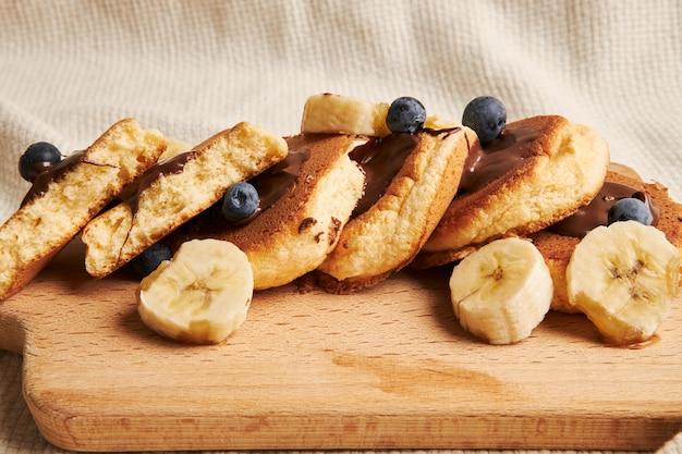 木の板にチョコレートソース、ベリー、バナナのパンケーキ