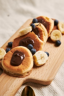 Pancakes with chocolate sauce, berries, and banana on a wooden plate