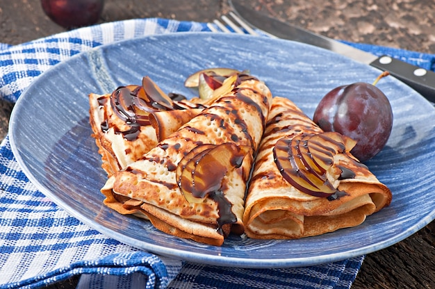 Pancakes with chocolate syrup and plums
