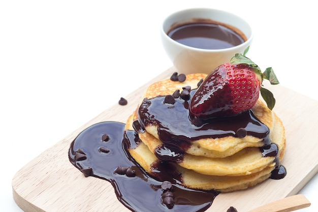 Pancakes with chocolate syrup and strawberry on white background