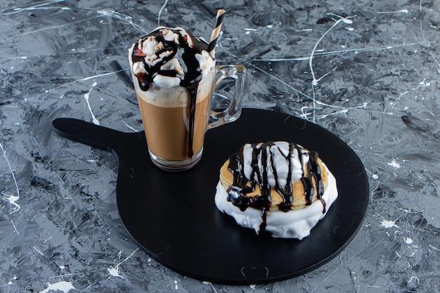 木の板にチョコレートのトッピングとコーヒーのグラスとパンケーキ。