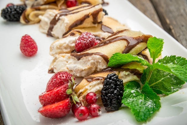 Pancakes with cottage cheese in the middle and berry sauce