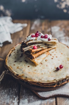 Pancakes with cranberries and sour cream on a wooden board in flour