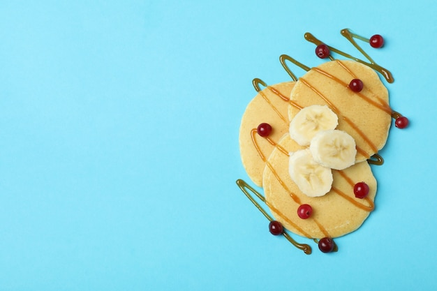 Pancakes with cranberry, banana and caramel on blue background