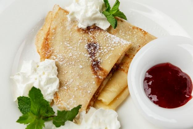 하얀 접시에 크림, 민트, 베리 소스를 곁들인 팬케이크. 전통적인 유럽식 아침 식사. 확대.