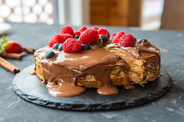 暗い背景にデザートフィリングとベリーのパンケーキ