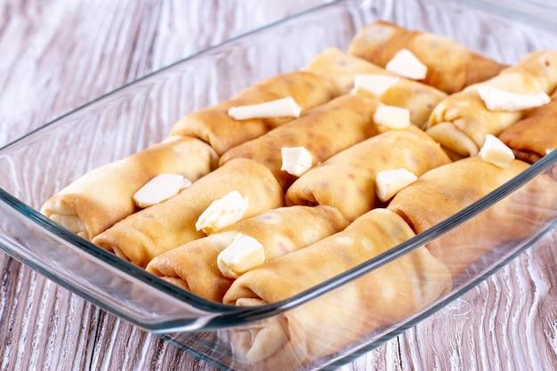 グラタン皿に詰めたパンケーキ。ロシアの伝統的な料理。詰め物のパンケーキ。肉、カッテージチーズ、マッシュルーム、ジャムのパンケーキ。