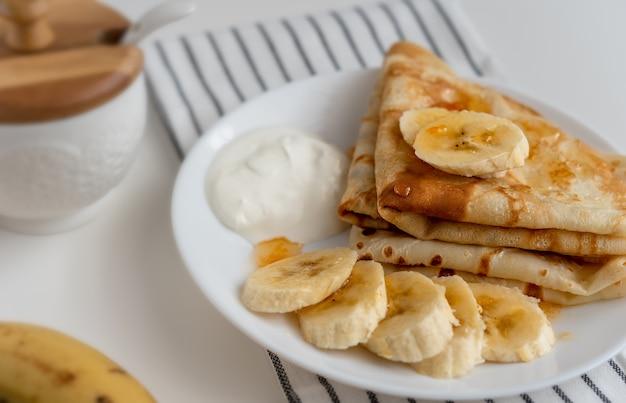 新鮮なバナナのパンケーキ、デザート用の白いプレートに天然ヨーグルト