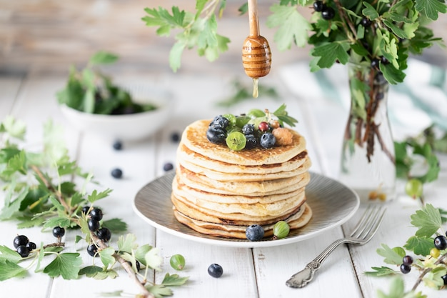 Pancakes with fresh berries of raspberries, currants, blueberries, with honey and tea