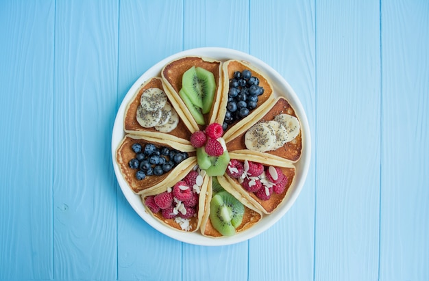 Pancakes with fresh berry on a blue wooden . pancakes with fruits. summer homemade breakfast.