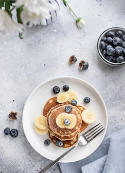 Pancakes with fresh blueberries, banana on a gray surface with white flowers. tasty breakfast. vertical image, top view