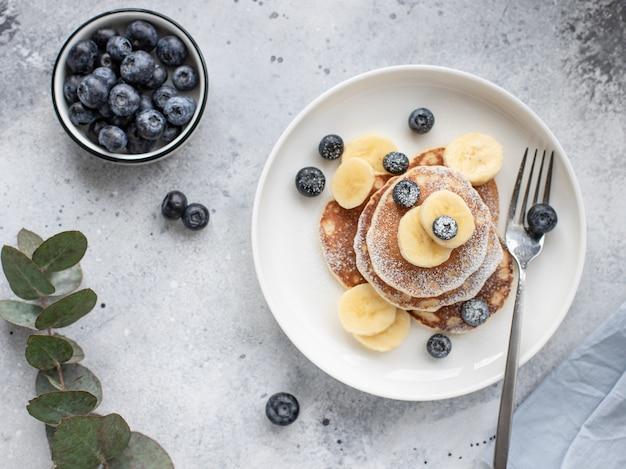 ユーカリの枝と灰色の表面に白いプレートにバナナ、新鮮なブルーベリー、パンケーキ。健康食品のコンセプト。水平方向の画像、平面図、平面レイアウト