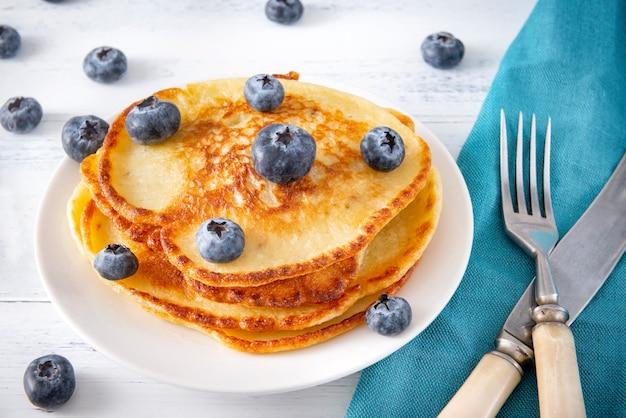 Блины со свежей черникой на тарелке, вилкой, ножом на синей салфетке на белой деревянной поверхности, вид сверху,