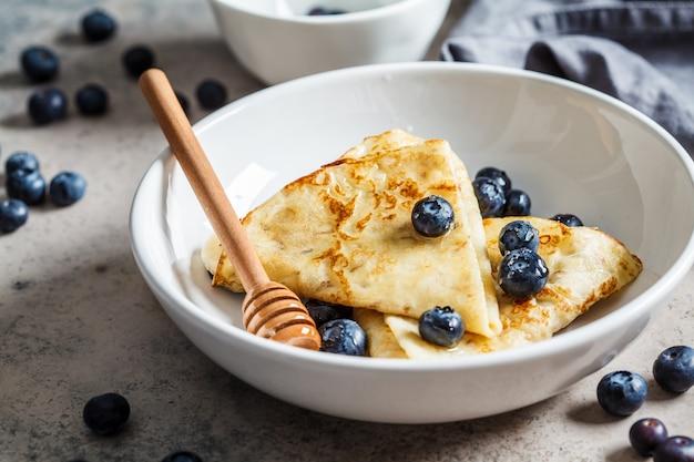 白い皿に果物と蜂蜜のパンケーキ。